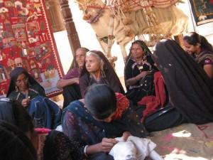 The women embroiders stitch together at the Kala Raksha center.