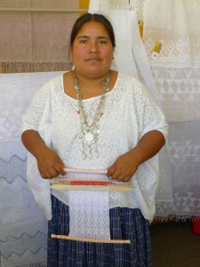 Amalia Gue, leader of the Ixbalam Ke cooperative, surrounded by brocade (inlay) weaving.