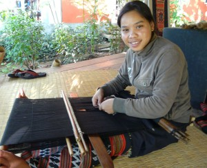Mone demonstrates Katu-style backstrap bead weaving at the Ock Pop Tok Living Crafts Centre. Note her beadwoven skirt.