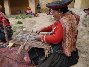 Accha Alta weaver working on a all natural piece while wearing a manta of many colors.