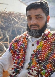 Aziz Khatri wearing a multi-colored, in-progress bandhani. The patterns are wound tightly with thread before dyeing.