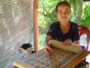Ms. Suxiong stops midstream in her application of wax onto handwoven hemp. Note the application tool (tjantung) in her hand.